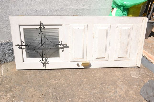 Porta de madeira maciça com janela e gradeamento de protecção