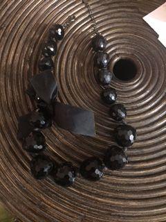 colar de bolas pretas e com laço