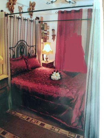 Cama de ferro com armação superior e cortinados.