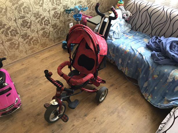 Детский трехколесный велосипед с родительской ручкой.