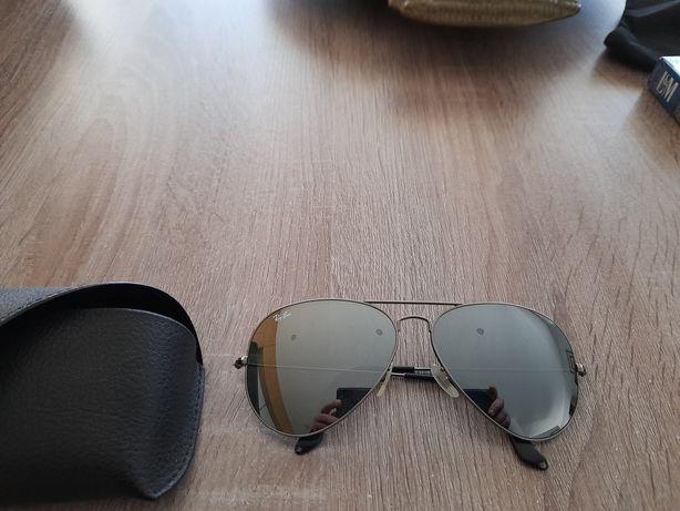 Óculos de sol espelhados Ray Ban e um par de lentes castanhas.