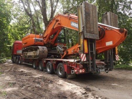 Transport maszyn rolniczych koparek na powrocie niskopodwozia z Europy